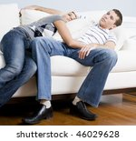 Woman snuggles up to man as they both relax quietly on a white couch. Horizontal format. - stock photo