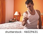 Man sits on his bed and looks pensively at a bottle of pills. Horizontal format. - stock photo