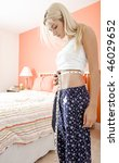 Woman standing in her bedroom and measuring her waist. Vertical format. - stock photo