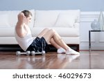 Man doing push-ups next to couch, with arm weights lying on the floor next to him. Horizontal format. - stock photo