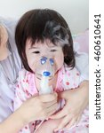 Small photo of Closeup of sad child having respiratory illness helped by doctor with inhaler. Pediatrician take care asian girl with asthma problems making inhalation with mask on her face at hospital. Child crying