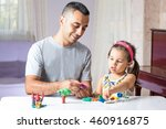 Little Girl Is Playing With Putty Together With Her Father - stock photo