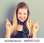 Small photo of Young woman crossing her fingers and wishing for good luck