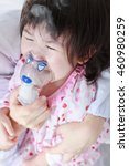 Small photo of Closeup of sad child having respiratory illness helped by doctorl with inhaler. Pediatrician take care asian girl with asthma problems making inhalation with mask on her face at hospital. Child crying