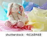 Adorable generic stuffed bunny surrounded by pastel colored tissue paper.  Close-up with shallow dof. - stock photo