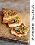 Small photo of Roasted sliced Turkey fillet with cheese, agaricus and parsley on a cutting board and an old wooden table. Tasty cooked Turkey meat. Lunch, dinner, picnic menu. Closeup
