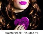 Pretty woman holding a heart-shaped box - stock photo