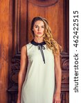Small photo of Portrait of American Lady in New York. Wearing sleeveless white dress with black collar, a beautiful business woman with long curly blonde hair standing by vintage style office door way, greeting you.