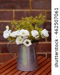 Small photo of Floral arrangement of white prairie gentians and delicate alchemilla mollis in a vintage metal jug on a wooden table against a brick wall