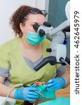 Small photo of Treatment of dental caries in a dental clinic. Woman dentist treats a patient tooth, looking through a microscope. Caring for teeth with toothache at the dentist.