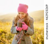 Small photo of Young smiling woman looking at coffee mug in her hands and enjoying the fall season. Woman in colorful striped scarf, purplish-red hat and gloves on nature background. Outdoor portrait in autumn.