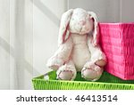 Adorable generic stuffed bunny with colorful storage containers.  Sunlight from side window for effect. - stock photo