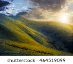 day and night composite image of green grass on hillside meadow in high mountains under the cloudy sky - stock photo