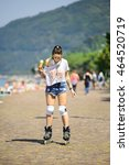Small photo of beautiful girl on roller skates eating traditional italian ice cream called Gelato in the waffle cone.