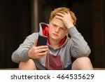 sad boy looking at mobile phone ...   Shutterstock . vector #464535629