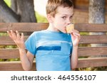 Small photo of boy eating a melting ice cream. child sitting on a park bench and eating ice cream. drops of chocolate ice cream melts fall on the boy's T-shirt. boy upset the appearance of stains on his clothes