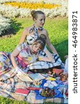 Small photo of Two retro-style girls on a summer picnic reading a book aloud