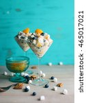 Small photo of Ambrosia fruit salad with marshmallows, blueberries, oranges, pineapple, pecans and coconut in martini glasses.