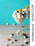 Small photo of Two servings of ambrosia fruit salad in martini glasses. Against turquoise background with scattered marshmallows, pecans, and blueberries. Landscape orientation.