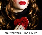 Pretty woman holding a red heart - stock photo