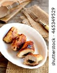 Small photo of Delicious fried Turkey meat rolls on a plate. Fork, cuisine board on old wooden table. Roasted Turkey breast rolls stuffed with cheese and agaricus. Festive food recipe. Rustic style. Vertical photo