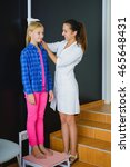 Small photo of female doctor measurement the girl stature at the clinic