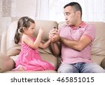 Little girl does not let her father smoke. - stock photo