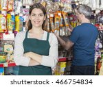 Stock photo saleswoman standing arms crossed while customer selecting produc 466754834