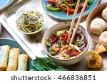 Small photo of Asian salad with chicken stir-fry, bok choy, cabbage and pepper, dim sum bowl, spring rolls, seaweed and beef salad with vegetables. Chinese style dinner. From above. Pan-asian food. Selective focus