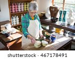 female potter arranging bowl on ... | Shutterstock . vector #467178491