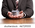 Businessman or estate agent at his desk holding a model house - stock photo