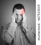 Small photo of Young Caucasian man with headache. Black and white stylized photo with red local ache spot