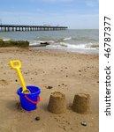 Kids bucket, spade and sandcastles on Felixstowe beach. - stock photo