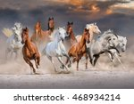 Stock photo horse herd run fast in desert dust against dramatic sunset sky 468934214
