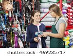 Stock photo happy girl buying toy from saleswoman in pet store 469235717