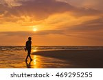 Man Walking Along The Beach At...