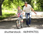 father teaching daughter ride... | Shutterstock . vector #469494701