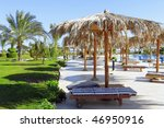Beauty landscape  of  sun umbrella, make of reed , bedstone and water pool. - stock photo