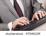 A man's hands typing on a dark keyboard - stock photo
