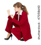 A woman in a red business suit sitting in a combat stance - stock photo