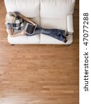 Full length overhead view of woman reclining on white couch and using a laptop. Vertical format. - stock photo