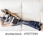 Overhead view of woman reclining on white couch and using a laptop. Horizontal format. - stock photo