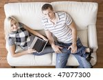 Cropped overhead view of couple relaxing together on white couch and looking up at camera, with woman using laptop and stretching out with her legs in the man's lap. Horizontal format. - stock photo