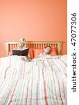 View of couple in bed, with woman reading book and man sleeping. Vertical format. - stock photo