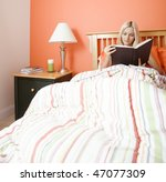 Blonde woman sitting in bed and reading a book. Square format. - stock photo