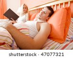 Woman holds book and watches man sleeping next to her. Horizontal format. - stock photo