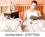 Man and woman reading side-by-side in bed. Horizontal format. - stock photo
