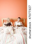 Man and woman reading side-by-side in bed. Vertical format. - stock photo