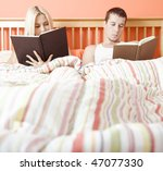 Man and woman reading side-by-side in bed. Square format. - stock photo