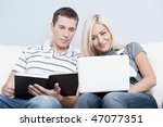 Man is reading, and woman is using a laptop, as they sit side by side on a white couch. Horizontal format. - stock photo